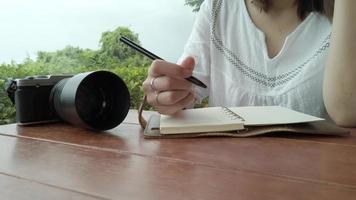 Woman writes notes on top of a wooden desk.