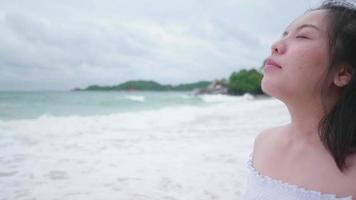 Mulher asiática de cabelo curto respira fundo na praia