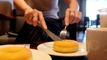 mãos de mulher cortando um donut.