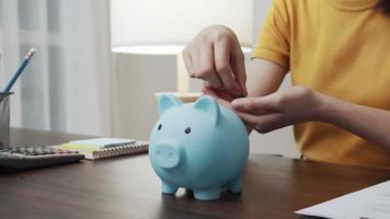 Frau legte Münzen in ein Sparschwein