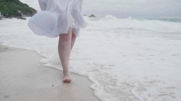 Cámara lenta de cerca corriendo piernas de mujer en la playa