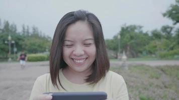 mulher asiática andando e brincando ao telefone