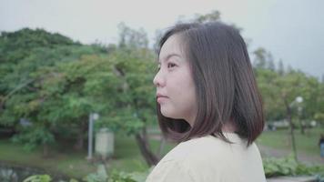 Mujer asiática relajante toma una bocanada de aire fresco en un parque al aire libre