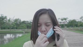 Mulher asiática tira a máscara facial enquanto faz uma chamada de celular