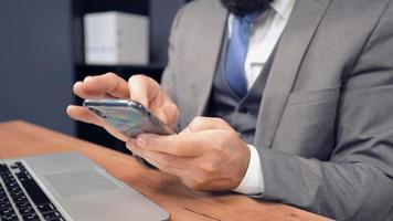 empresário de meia-idade usando smartphone no escritório