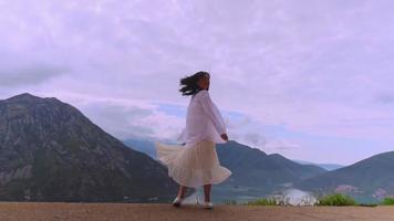 femme en vêtements blancs tournant sur la colline