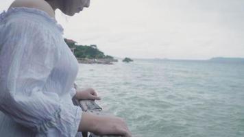mulher asiática em câmera lenta tocando uma ponte de madeira na praia video