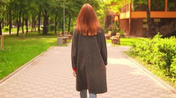 Redheaded woman walking along the path in slow motion video