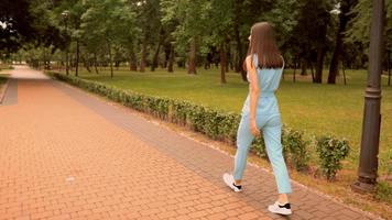 Back View of A Woman Walking on A City Park