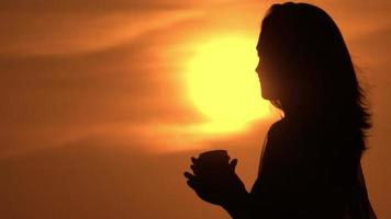 A Woman Holding a Cup of Coffee While the Sun Is Rising