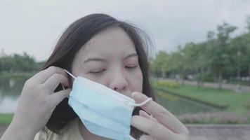 mujer asiática, llevando, máscara facial, en el parque