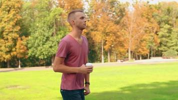 Young Man Walks in Park Holding a Cup of Coffee