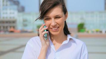 mulher alegre usando celular em meio urbano