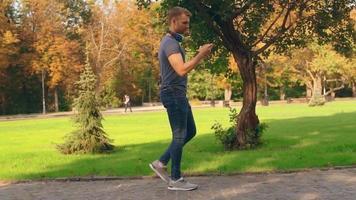 un chico camina en un parque de la ciudad mirando su teléfono