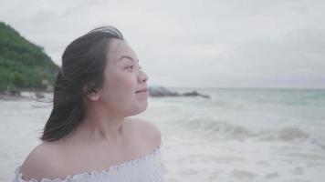 Mujer asiática en cámara lenta respira profundo en la playa