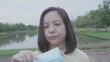 Mujer asiática molesta por usar mascarilla en el parque