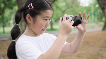 criança asiática menina fotografia natureza com câmera.