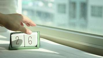 mano que cambia el bloque de calendario de madera blanca del 26 al 27