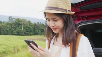 mulher usando smartphone perto de um carro
