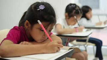 menina asiática escrevendo na sala de aula na escola.
