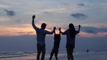 silhuetas de família asiática feliz na praia.