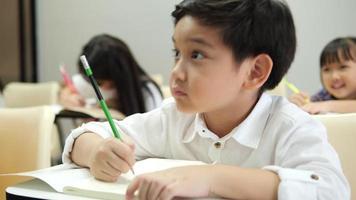 crianças asiáticas estudando na sala de aula da escola.
