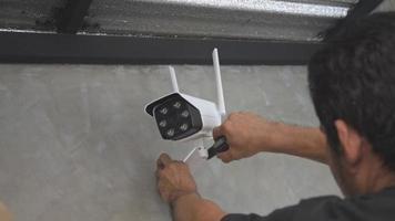 técnico instalando una cámara CCTV inalámbrica en la pared.