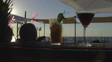 Multiple cocktails on a bar with sun setting into the sea in the background video