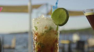 Cocktail auf einer Bar mit Sonnenuntergang im Meer im Hintergrund video