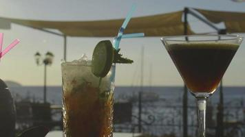 Multiple cocktails on a bar with sunset in the background video