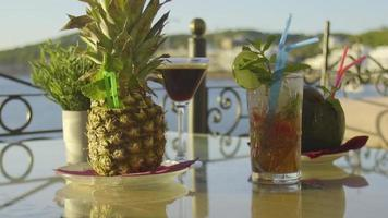 Sunlit cocktails on a table with sea in the background