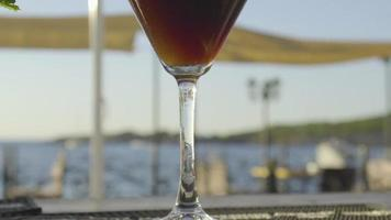langsames Mo von Cocktail auf einer Bar mit Sonnenuntergang im Hintergrund video