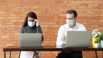 A Couple Wearing Face Masks and Working on Laptops video