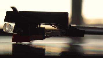 uma agulha de vinil gravadora de uma perspectiva lateral durante o pôr do sol