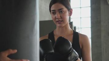 mujer asiática probando el boxeo por primera vez.
