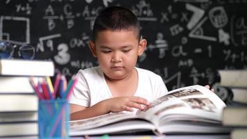 asiatisches Kind, das ein Buch öffnet und liest