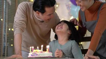 Girl Blows Candles with Family at Home video