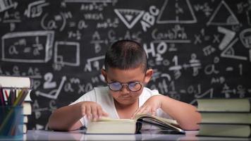 criança asiática de óculos lendo sentada na mesa