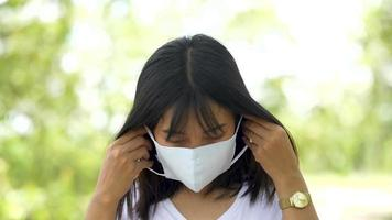 Young Asian woman wearing protective facial mask in the forest