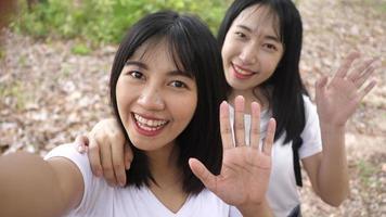 Dos jóvenes mujeres asiáticas sonrientes tomando un video selfie