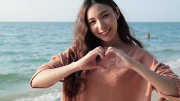 Mulher bonita asiática fazendo formato de coração com as mãos na praia