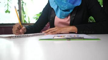 Busy business Arab woman reviewing reports and charts video