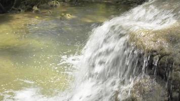 el agua dulce fluye desde la roca hasta un estanque natural