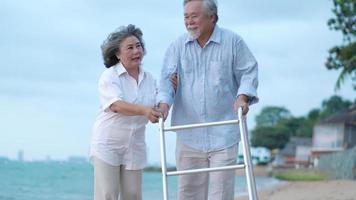 Asian couple senior walking with a walker at the beach.