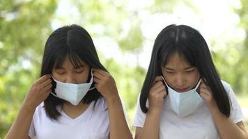 duas jovens mulheres asiáticas usando máscara facial protetora na floresta video