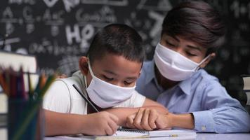 Young female teacher wearing a mask teaches boys to write letters in the classroom