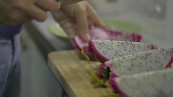 mulher cortando fruta madura do dragão com uma faca