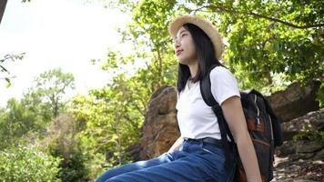 Beautiful asian woman backpacking sitting and relaxing in nature