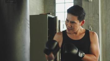homem atlético asiático de boxe no ginásio.