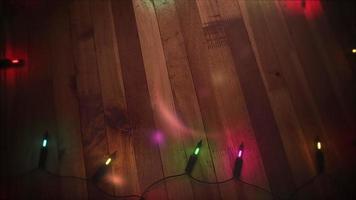 Cadena de luces de colores sobre un piso de madera video